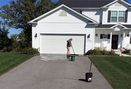 Guy Brushing on Sealcoating For a Driveway